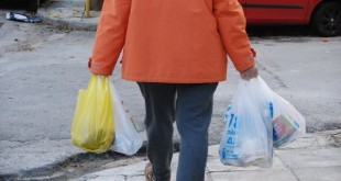 A man carries his purchases in plastic bags across the street in Athens, Greece, 31 December 2017. Starting from 01 January 2018 plastic bags have be purchases at a price of 4 cents, and from 2019 on they are going to cost 9 cents each. The measure against contamination is needed urgently: Evaluations estimate that Greeks take more than 400 of these bags home every year. Photo by: Alexia Angelopoulou/picture-alliance/dpa/AP Images